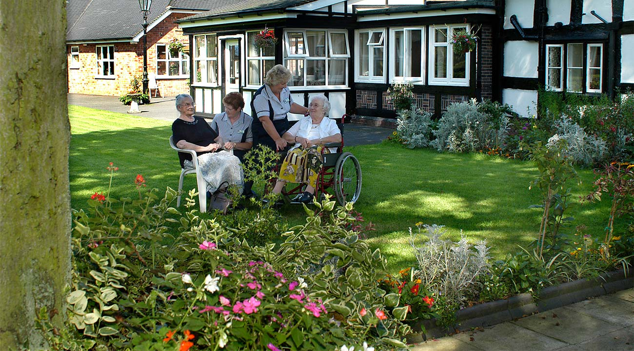 Heyfields residents enjoying the gardens and sunshine with care staff